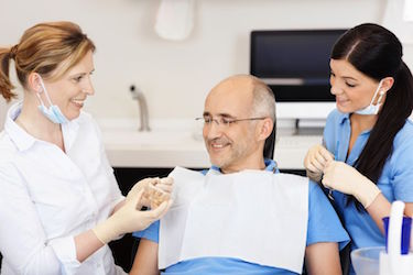 21246880 - dentist explaining teeth model to male patient at clinic